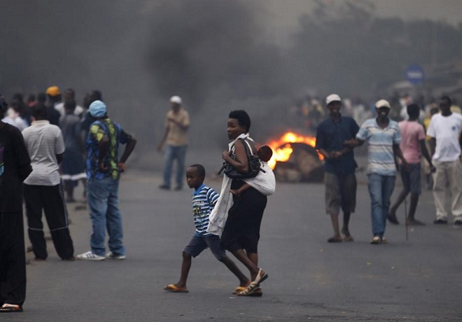 Woman crosses a street with her children near a burning barricade in Bujumbura