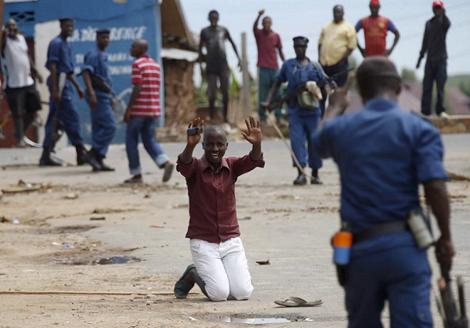 Protester kneels in front of a policeman during a protest against Burundi President Pierre Nkurunziza and his bid for a third term in Bujumbura
