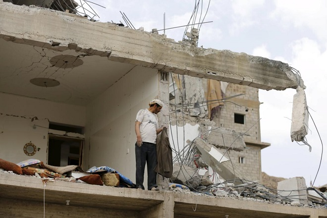 A man stands in a building destroyed by Saudi-led air strikes in Yemen's capital Sanaa September 7, 2015. Jets belonging to a Saudi-led coalition killed at least 20 people at a wake in northern Yemen on Sunday, local tribesmen said, as warplanes pounded Houthis and other forces behind a missile strike that had killed dozens of Gulf Arab soldiers. REUTERS/Khaled Abdullah