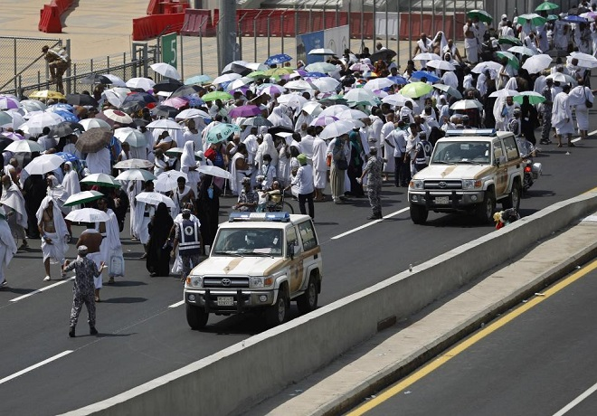 Police vehicles drive past pilgrims on a road in Mina, near the holy city of Mecca September 24, 2015. REUTERS/Ahmad Masood
