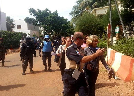 BAMAKO, MALI - NOVEMBER 20 :  Malian security forces escort a hostage freed from the Radisson Blu hotel in Bamako on November 20, 2015. Gunmen have taken 170 hostages at Radisson Blu Hotel in Mali on November 20, 2015. (Photo by Moussa Bolly/Anadolu Agency/Getty Images)