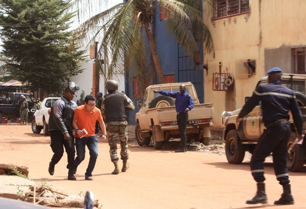 A Mali trooper, left, assist a hostage, second left, to leave the scene, from the Radisson Blu hotel to safety after gunmen attacked the hotel in Bamako, Mali, Friday, Nov. 20, 2015. Islamic extremists armed with guns and throwing grenades stormed the Radisson Blu hotel in Mali's capital Friday morning, killing at least three people and initially taking numerous hostages, authorities said.  (AP Photo/Harouna Traore)