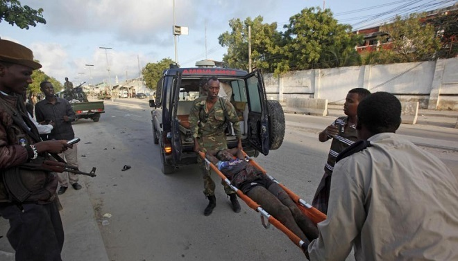 Somali policemen carry a wounded person to an ambulance outside the Sahafi Hotel in Mogadishu, Somalia Sunday, Nov. 1, 2015. A Somali police officer says an explosion followed by heavy gunfire has been heard at a hotel in the Somali capital. The hotel is often frequented by Somali government officials and business executives. (AP Photo/Farah Abdi Warsameh)