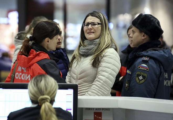A woman reacts next to Russian Emergencies Ministry members at Pulkovo airport in St. Petersburg, Russia, October 31, 2015. REUTERS/Peter Kovalev