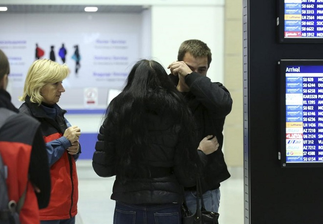 A man reacts next to Russian Emergencies Ministry members at Pulkovo airport in St. Petersburg, Russia, October 31, 2015.  REUTERS/Peter Kovalev