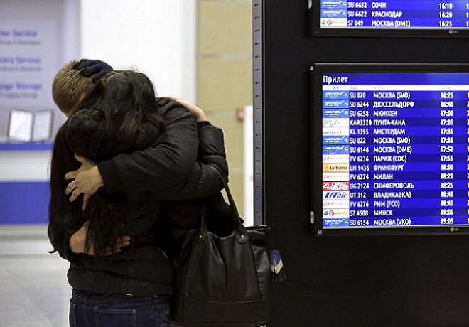 A couple embraces next to a flight information board at Pulkovo airport in St. Petersburg, Russia, October 31, 2015. REUTERS/Peter Kovalev