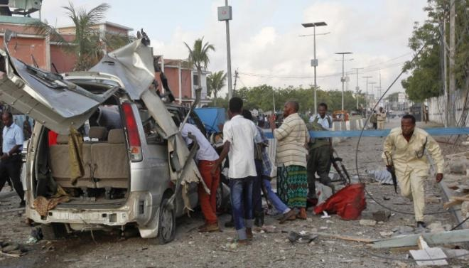A Somali policeman runs through the wreckage outside the Sahafi Hotel in Mogadishu, Somalia, Sunday, Nov. 1, 2015. A Somali police officer says an explosion followed by heavy gunfire has been heard, thought to have been caused by a suicide car bomb, at the hotel often frequented by Somali government officials and business executives. (AP Photo/Farah Abdi Warsameh)