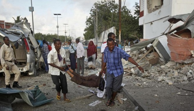 Somali men carry a wounded person to an ambulance outside the Sahafi Hotel in Mogadishu, Somalia Sunday, Nov. 1, 2015. A Somali police officer says an explosion followed by heavy gunfire has been heard at a hotel in the Somali capital. The hotel is often frequented by Somali government officials and business executives. (AP Photo/Farah Abdi Warsameh)